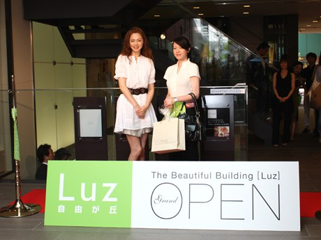 「Luz自由が丘」開業一番乗りの利用客に記念品を贈呈する川原亜矢子さん
