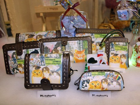 久下さんが描く個性豊かな猫とその世界を商品化した「マンハッタナーズ」(写真は主力商品の財布・パスケース・キーケースなど)