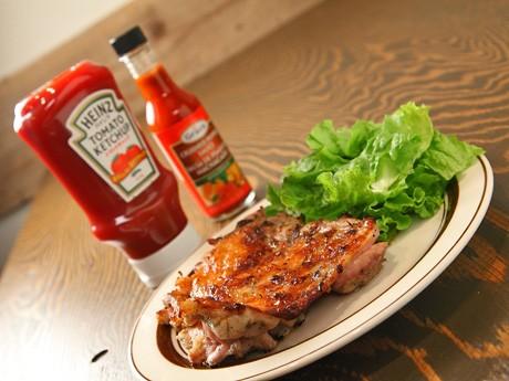 ハーブやスパイスに一晩漬け込んだ国産鶏もも肉の表面を直火グリラーで一気に焼き上げた、同店メーンメニュー「ジャークチキン」