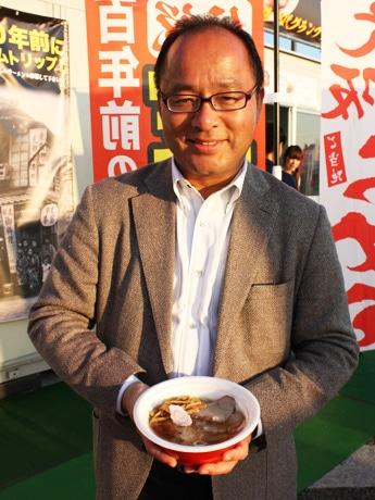 イベント実行委員長の大崎裕史さんが手にしているのが「日本初の『醤油(しょうゆ)ラーメン』」ラーメンブース3番で提供