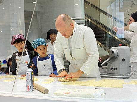 全面ガラス張りのキッチンで子どもたちとクロワッサンを成形するクリストフ・ヴァスールさん