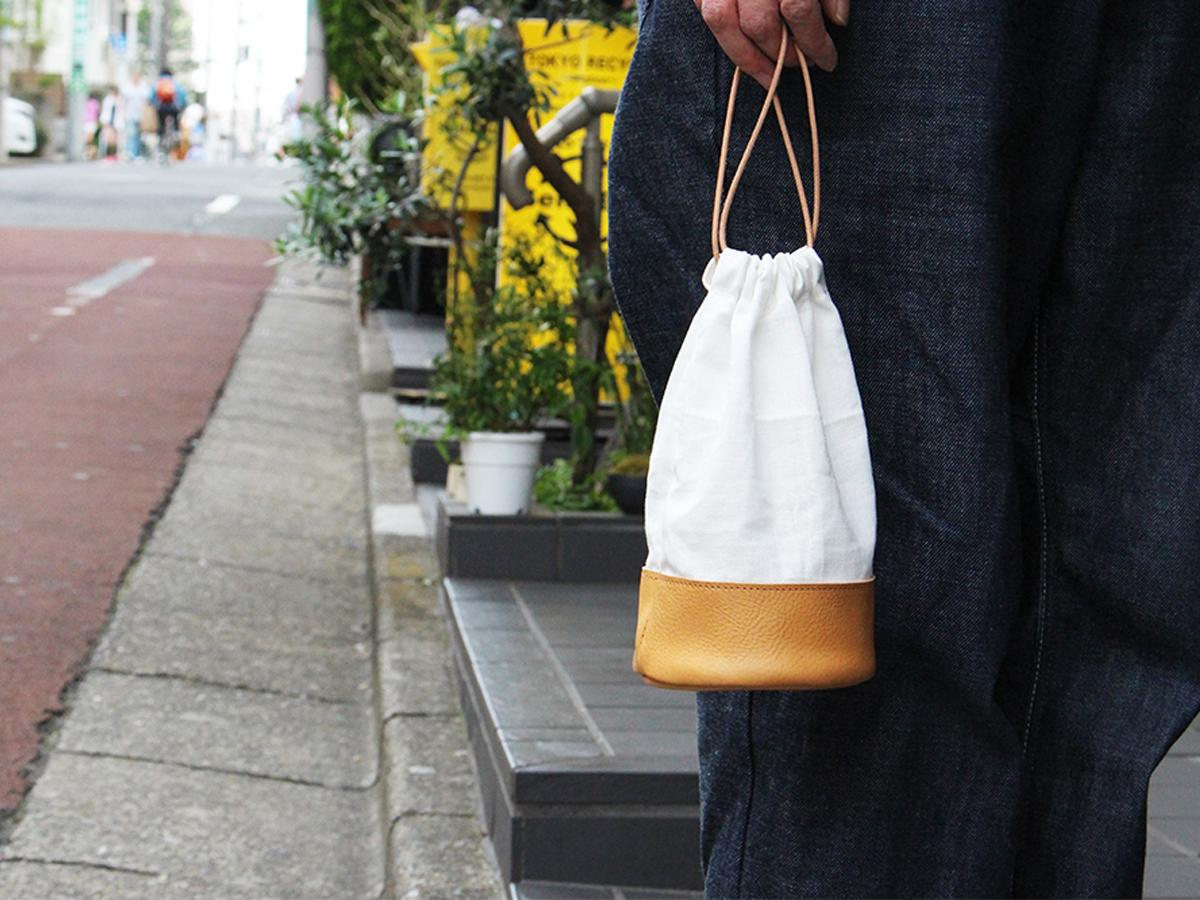 財布やスマホなどを入れて身軽に持ち歩ける「革工房 hibi」の巾着タイプのミニバッグ