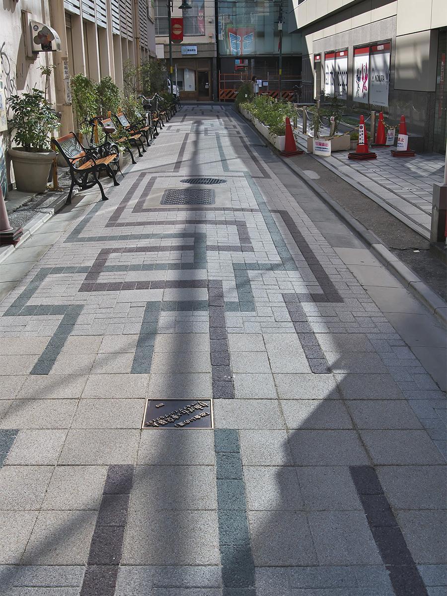 緑と赤の2色のラインが所々交差するように延び、真ん中付近に設置した銘板部分で「出会う」、自由が丘「出会いの道」