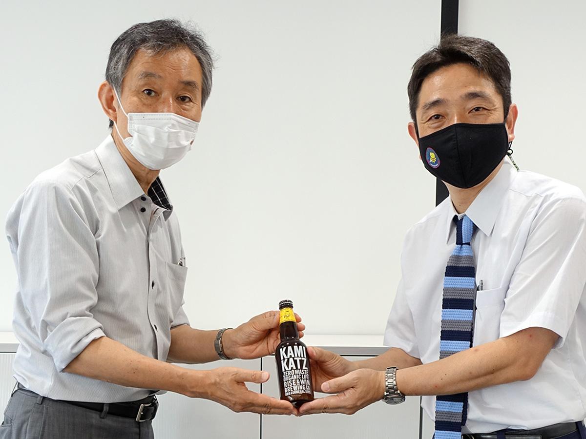 寄贈された「丘ばちビール」(写真左から)玉川医師会の阿部晃一事務長、自由が丘商店街振興組合の中山雄次郎事務長