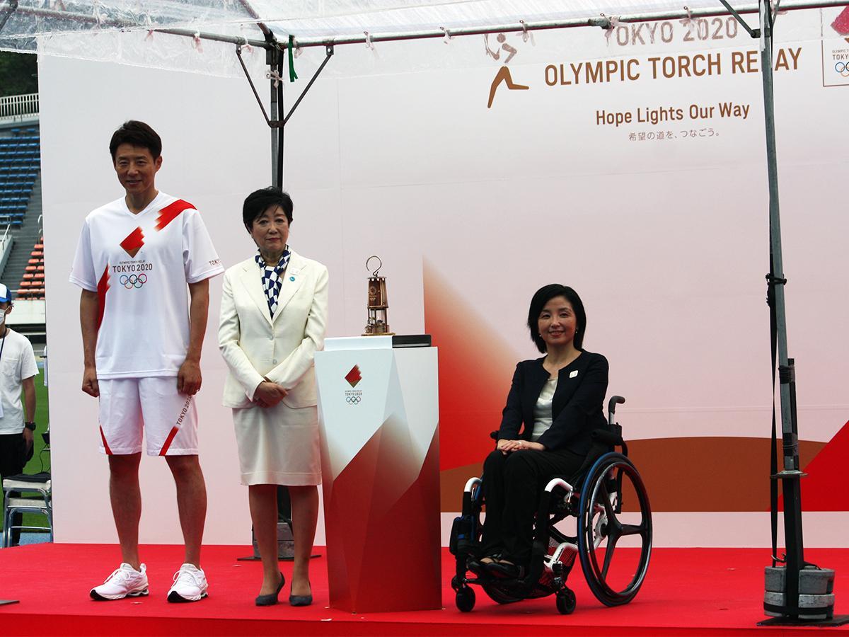 架台に置かれた東京五輪の聖火ランタン。(写真左から)松岡修造さん、小池百合子知事、田口亜希さん