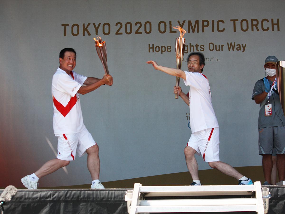 聖火トーチをバットに見立ててスイングするパフォーマンスを披露した巨人の原辰徳監督(写真左)