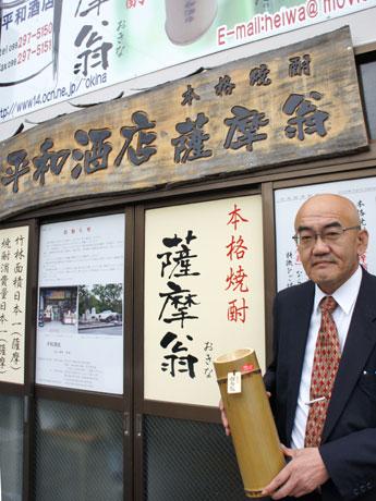 店主の諸平和也さん。竹に入った焼酎「薩摩翁」は平和酒店のプライベートブランド。
