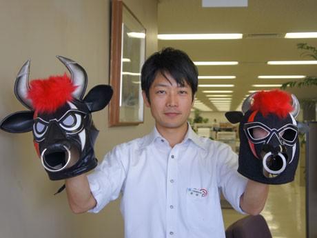 ギュージンガー・ブラックのマスクを持つ東條さん。左はネーミング発表時に実際に使われたもの。プレゼントは右のキッズ用。