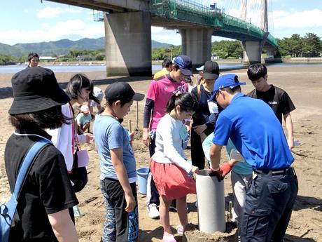 学生と子どもたちが一緒に砂の造形を作る様子