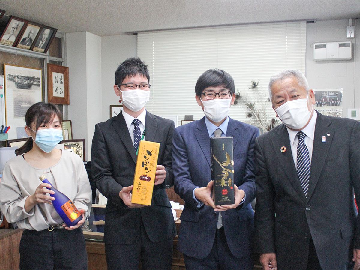 村長室で辞令を受けた「特酒営業部隊」の隊員と大山辰夫村長(右)