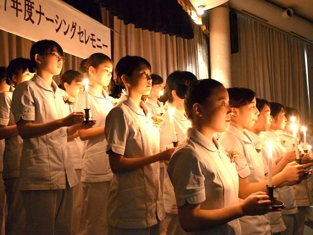 キャンドルを持ち、ステージで並ぶ看護学生