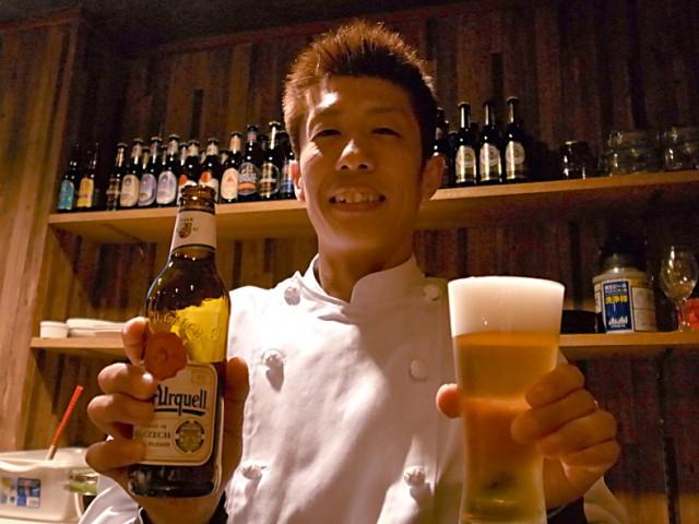 ビール瓶を持って説明する店主の山本さん