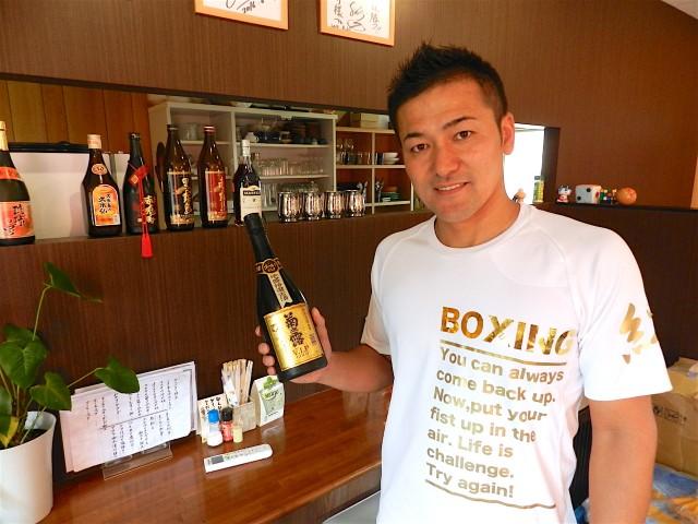 琉球泡盛を持つ店主の熟山さん
