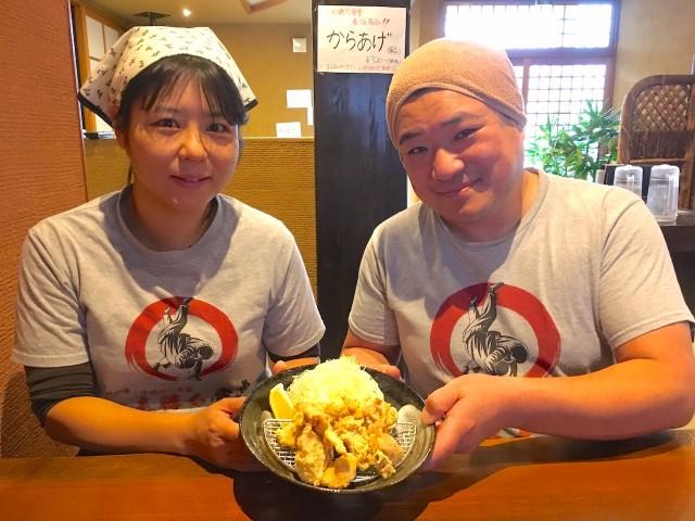 一番人気メニューのから揚げを持つ吉田さん夫妻