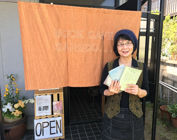 新調したのれんの前で笑顔を見せる店主の朝山節子さん
