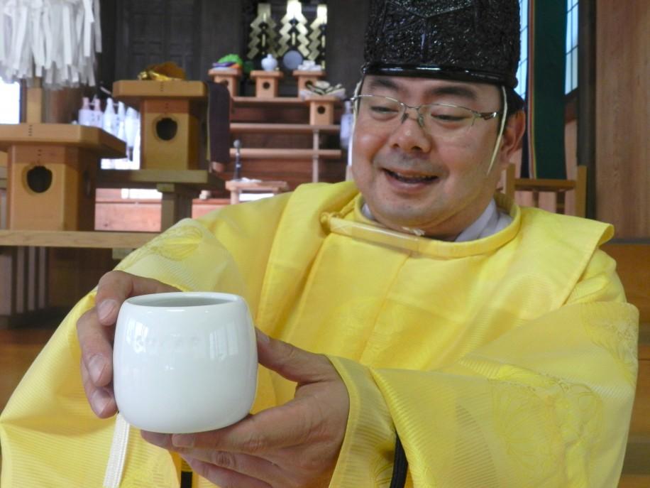 神具として使っていた砂糖壺を持つ宮司
