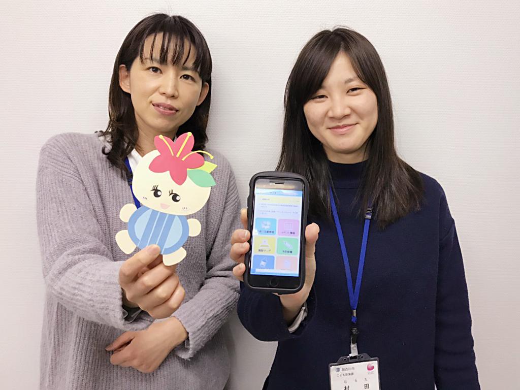 キャラクター「かこたん」を持つ梅谷美穂さんとスマホを持つ村田麻実さん