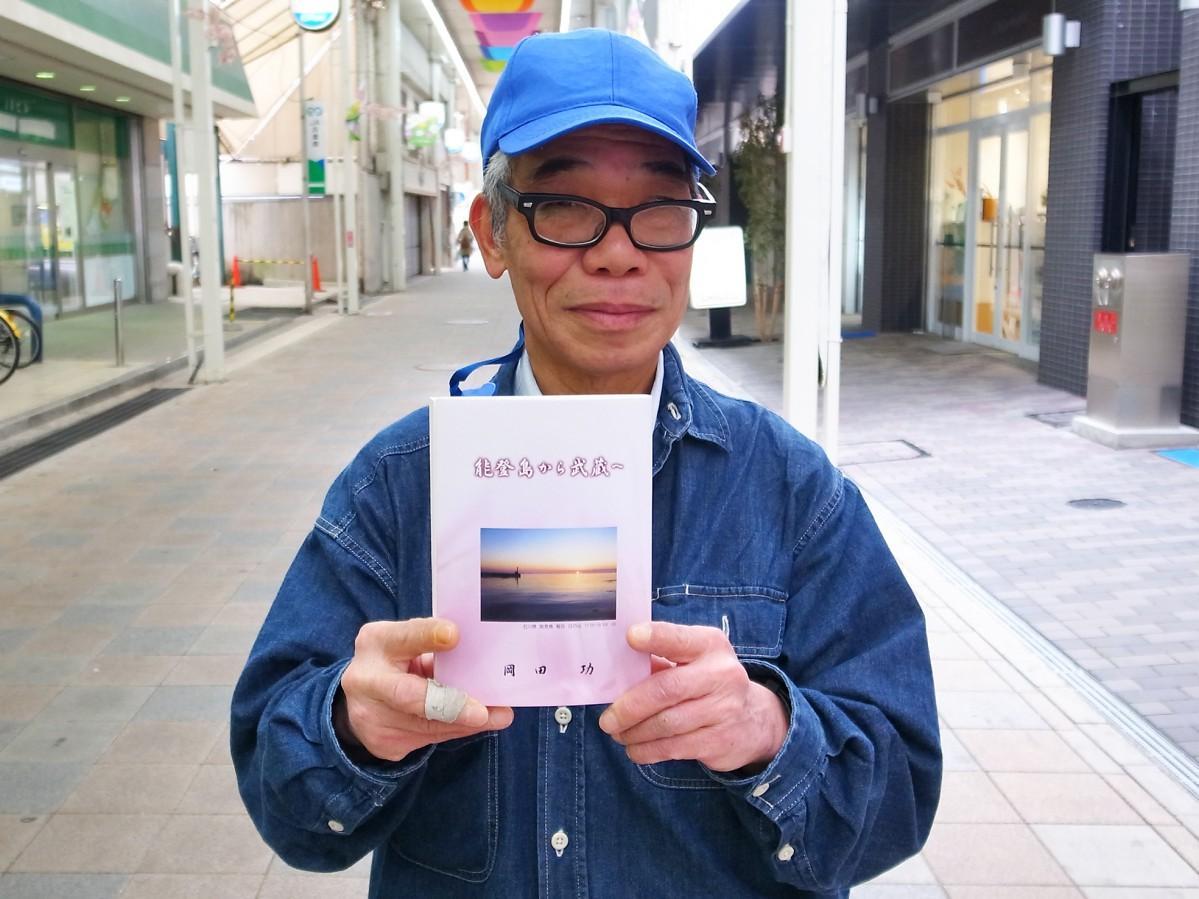 完成した本を持つ岡田さん