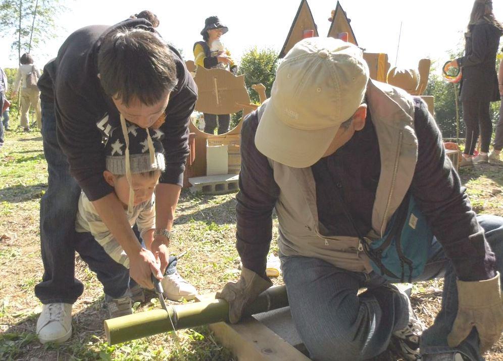 竹をノコギリで切る体験をする来場者