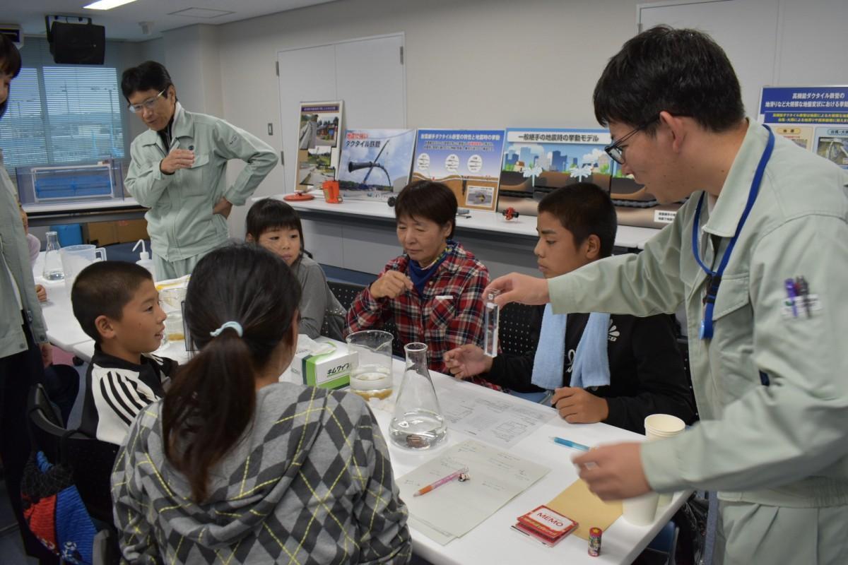 水の安全性について説明を受ける参加者
