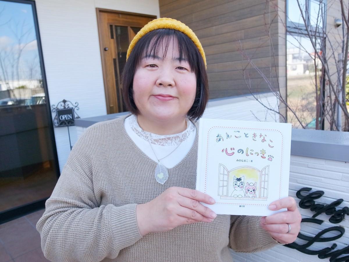 出版した本を持つ三野さん
