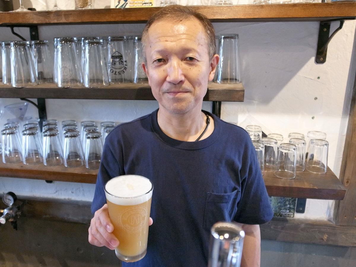 同店で醸造したクラフトビールを持つ大西さん