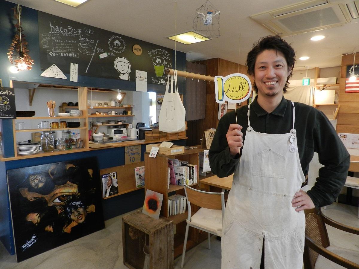 作品を展示する「はま茶」で、自身が制作した10周年ロゴマークでPRする「はま茶」代表の濱田さん