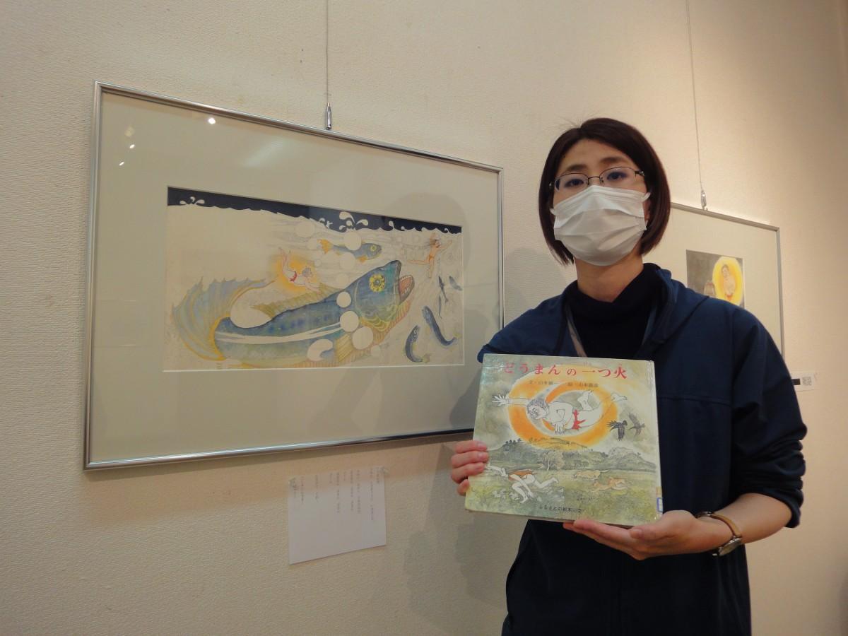 絵本を手にする企画担当の東条美咲さん