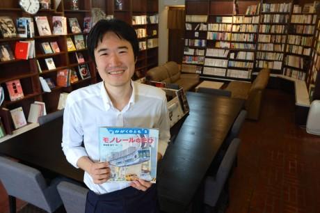 店長の和田さん。壁一面の本棚は40年前に桜材で作られたものをそのまま使った