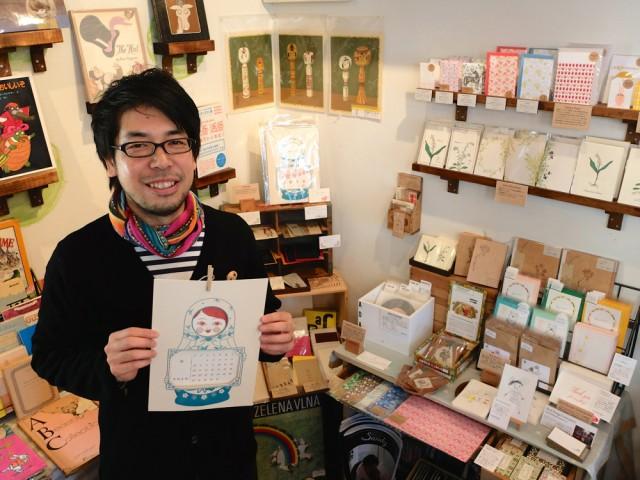 「つるぎ堂」のマトリョーシカをモチーフにしたカレンダーを手にする店主の荘田賢介さん