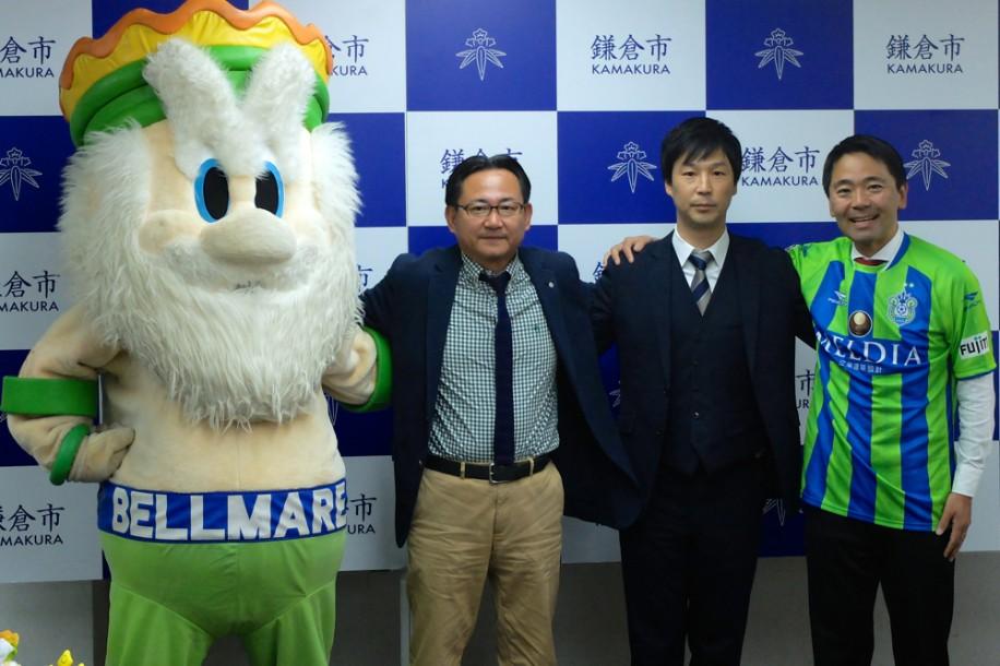 肩を組む(右から)松尾市長、中里さん、真壁会長、マスコットキャラクターのキングベルI世