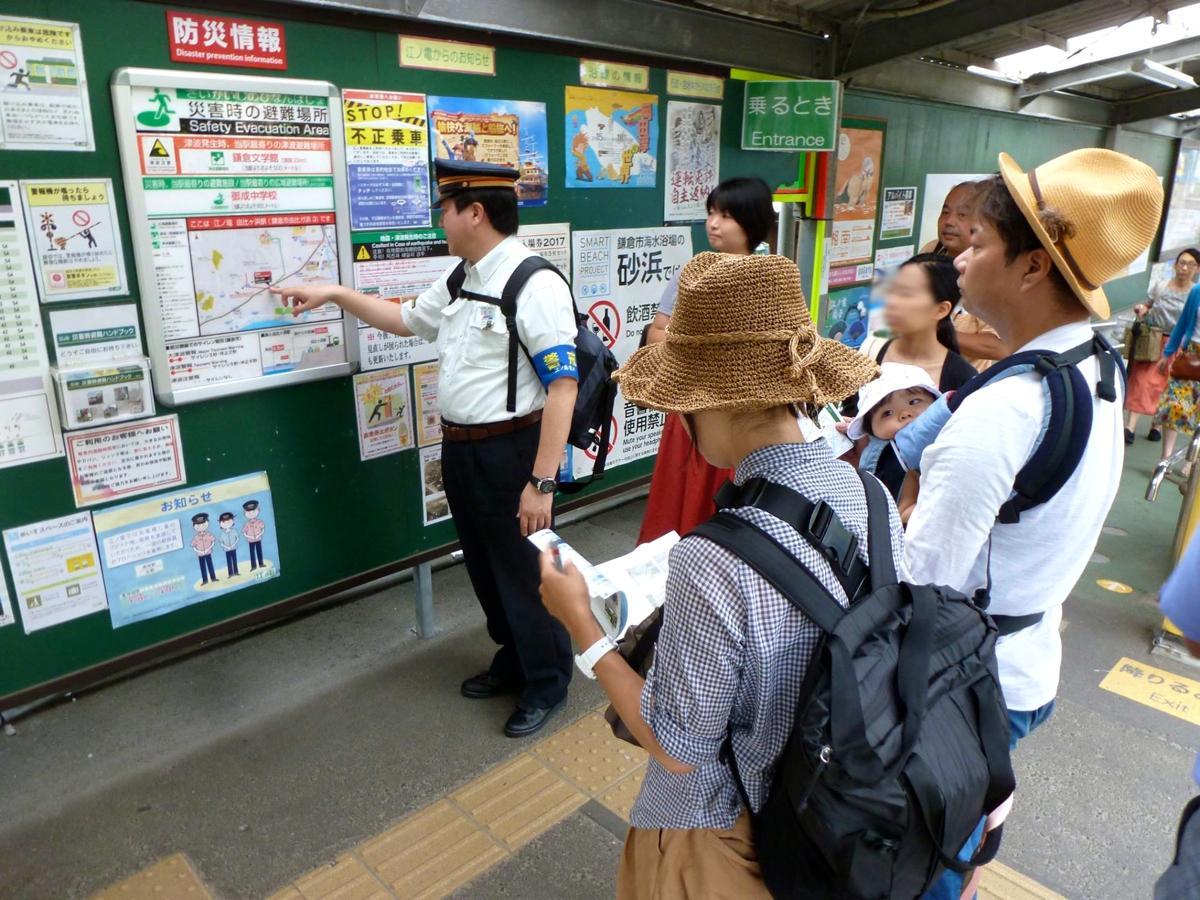 駅のホームに掲示されている地図で避難場所までのルートを説明する江ノ電の職員(前回の様子)