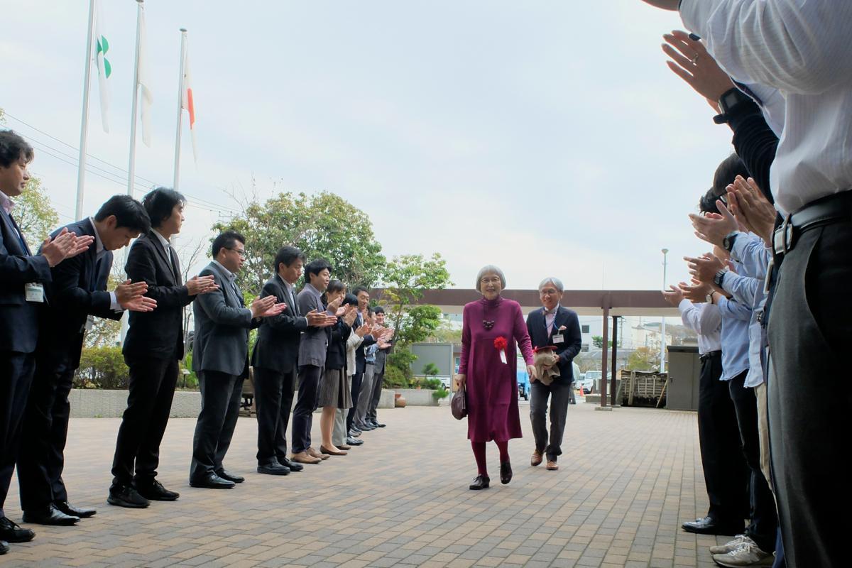 市庁舎前で職員や市民に拍手で迎えられ表彰式に向かう角野さん。ブドウ色のワンピースは自らのデザインという