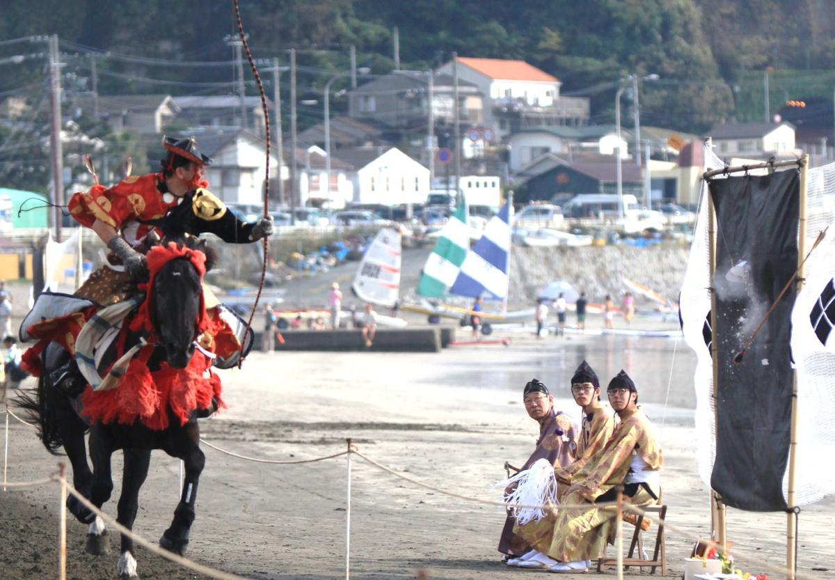 見事に命中した瞬間。伝統を感じる装束の向こうにヨットの帆が見える風景が海岸ならでは(前回の様子)