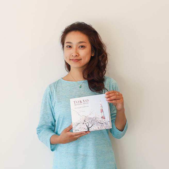 「TOKYO MINDSCAPES」を手にする松井さん。日本とニューヨークを行き来し活動中
