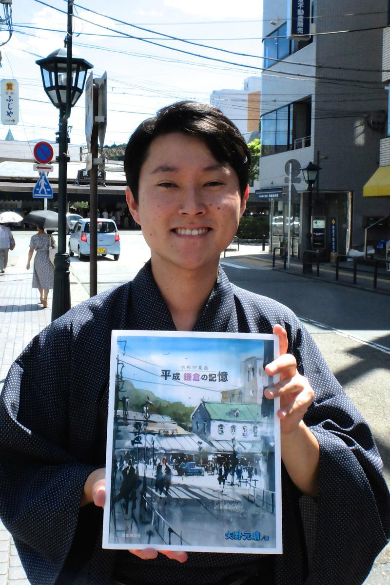 表紙を描いた鎌倉駅西口で、画集を手にする矢野さん。和服がトレードマーク