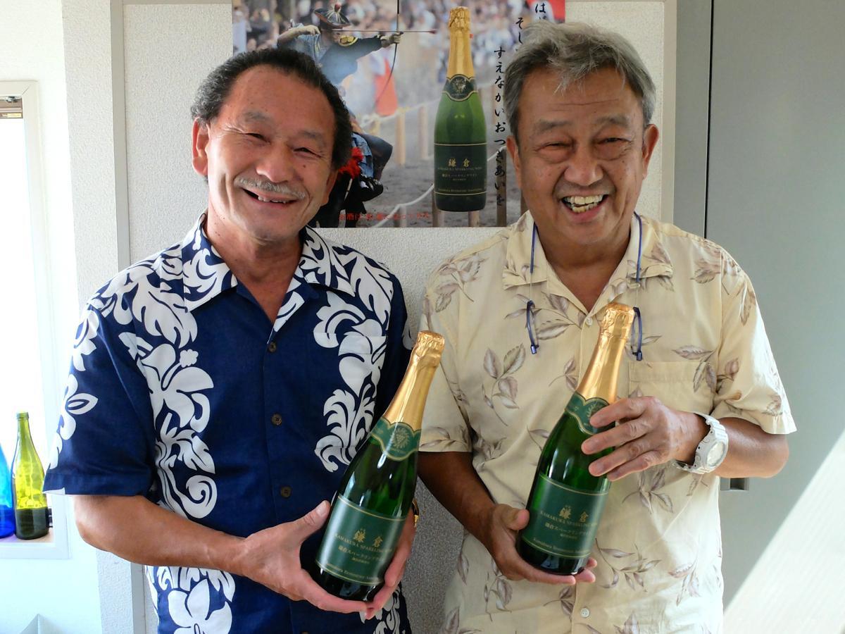 届いたばかりの商品を手に笑顔になる桑原さん(左)と柿澤さん。後方は取扱店に掲出するポスター