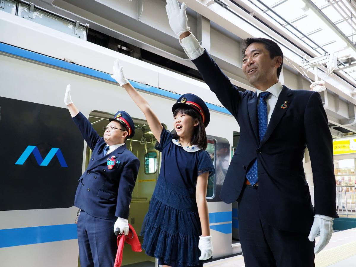 「出発進行」と合図する石井さん(中)と松尾市長(右)。駅構内には拍手が響いた