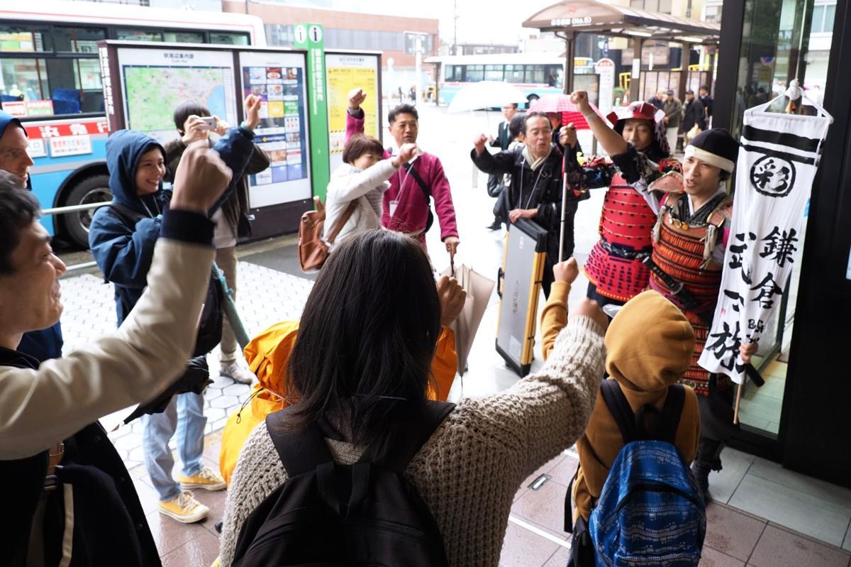 出発前、鎌倉駅前で気勢を上げる参加者たち。右端の甲冑(かっちゅう)姿が高野さん