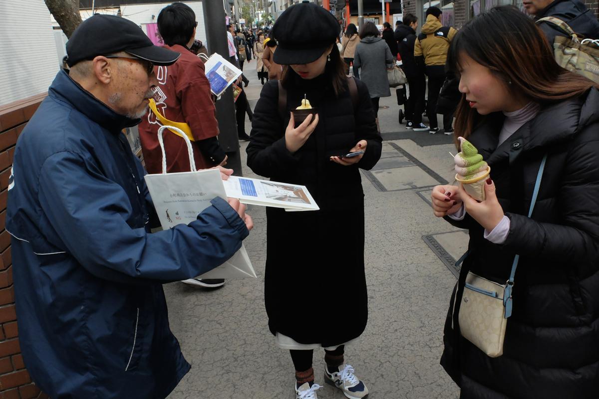 「おもてなし袋」を配布する高橋会長。食べ歩きしていた観光客が話に聞き入る