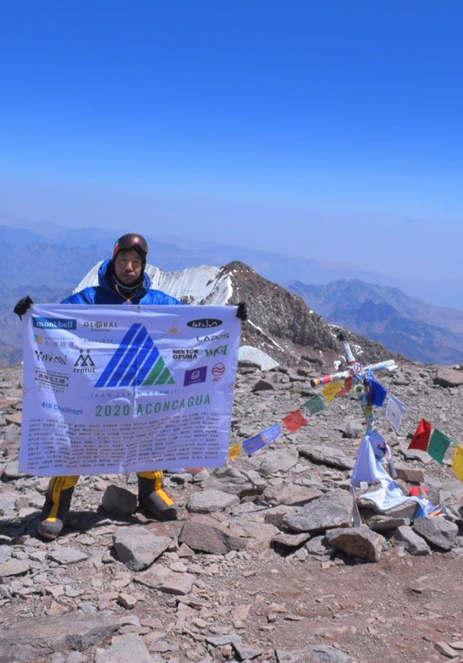 アコンカグア頂上でスポンサーや支援者の名前が入ったフラッグを手にする西川さん