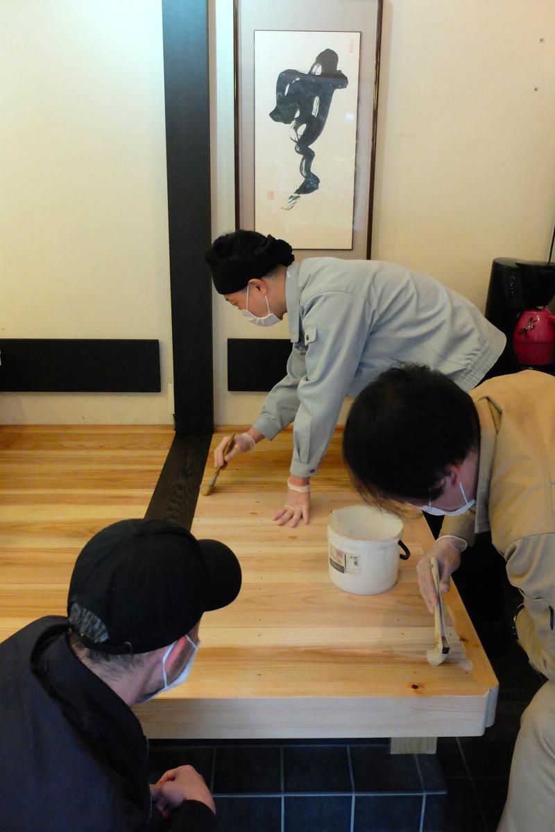 組み上がった小上がりの床にペンキを塗る福澤さん(奥)と藤井さん