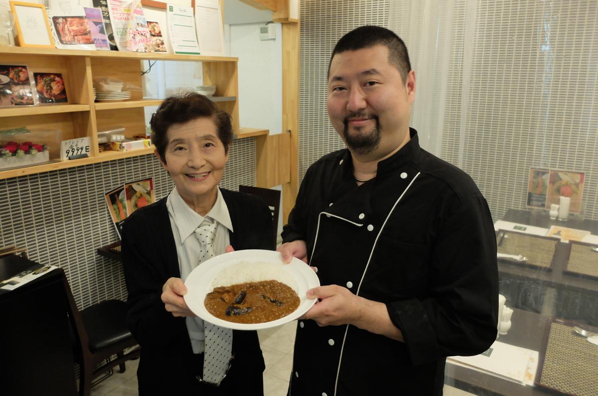 「ナスとひき肉のカレー」を手にする古川親子。「商売なので最低1円と消費税は頂きます」と笑う
