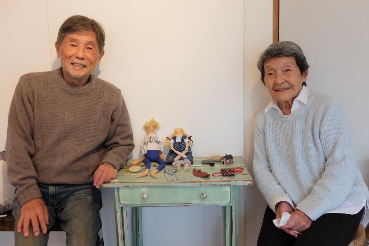 作品を並べたグリーンの机も実は三重子さんの作品。中央の人形はまるで2人がモデルのよう