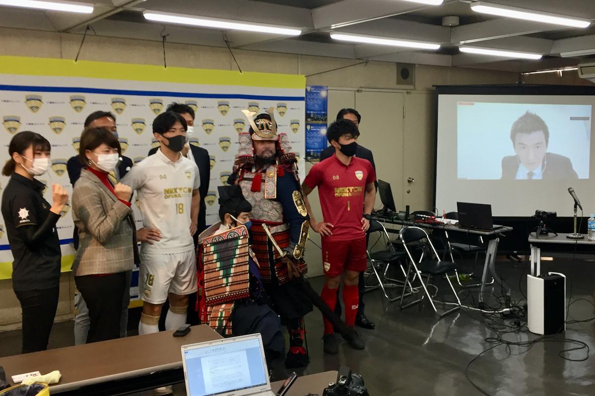 記者会見後の記念撮影は選手や関係者のほか、賛同者の「鎌倉もののふ隊」の姿も。代表の四方さんはシンガポールからオンラインで参加(右スクリーン)