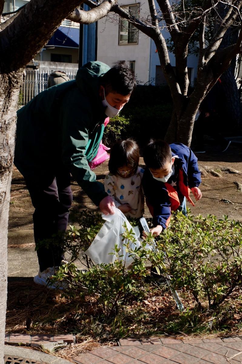 初参加の家族が植え込みの中にゴミを見つけ協力して拾う