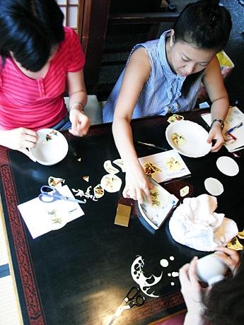 白生地にシールを貼ってオリジナルの九谷焼を制作する参加者たち