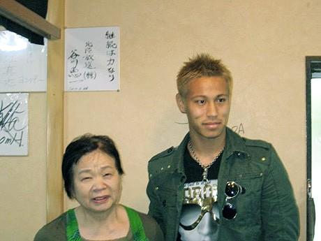 「金沢のお母さん」徳本さん(左)と記念写真に収まる本田選手(「新潟」提供)