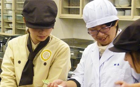 石川菓業青年会会員とともにケーキを試作する学生(1月17日)(北陸学院大学提供)