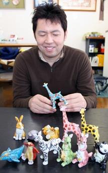 「くたに動物園」を企画した中田店長。手にしているのは1番人気の青色のキリン